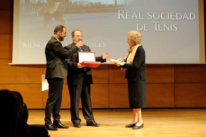 El presidente de la Real Sociedad de Tenis, Rafael Peregrín, recibe la Mención de manos de María Teresa Cuadrado